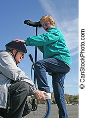 Seniors and Unicycle - Senior Man giving senior Woman a...