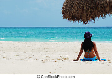 beach - beautiful brunette tanning at white sandy beach