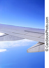 Airplane wing - Wing of an airborne airplane with blue sky...