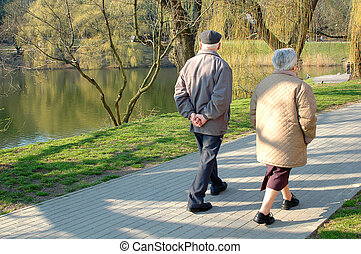 Seniors walking - A couple of seniors walking in the park,...