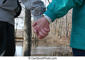 Senior hand hold - Senior couple strolling through the...