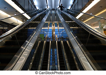 Escalators in airport - Motion of people with escalators in...