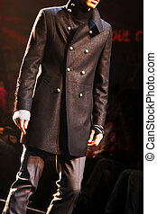 Male model on the catwalk in a black jacket and pants.