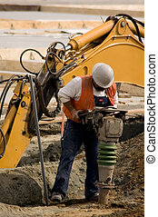 Tamper - A construction worker using a large soil tamping...