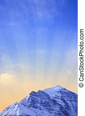 Mountain sunrise - Sun rising behind a big snowy mountain -...