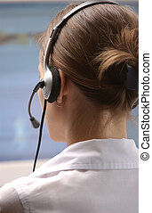 Customer Services - Young woman operator with headphone and...