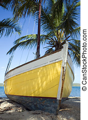 Sloop - A yellow-hulled sloop sits on a tropical beach.