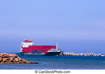 Cargo ship with red containers entering port