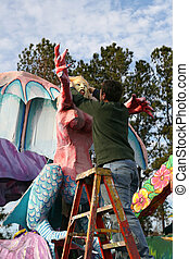Mardi Gras - krewe member puts the finishing touches on a...
