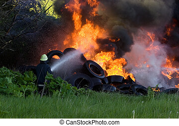 Firefighters battle with burning tires