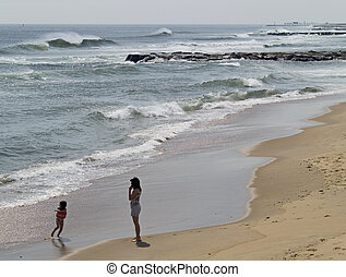 Day at the Beach - A mom looks on as her daughter plays in...