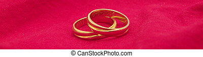 wedding rings - two wedding rings on a red cloth background