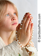 Prayer - Little blond girl counting the rosary