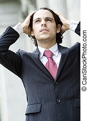 Business Troubles - A young businessman looking troubled...