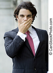 Business Silence - A young businessman covering his mouth...