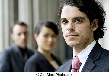 Business People - A young businessman standing in front of...
