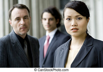 Serious Business People - A serious businesswoman standing...