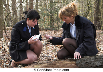 Forensic research - Two female police officers working on...