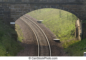 railway bridge - Railway tracks curve beneath a stone bridge