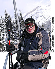 Happy skier - Happy man on a chairlift at downhill ski...