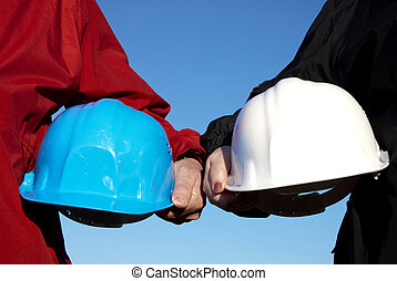 helmets - two hard-hats (blue and white color) focus on hand...