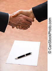 The deal - 2 hands shaking with a blank contract and pen