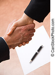 Shake on it - 2 hands shaking with a blank contract and pen