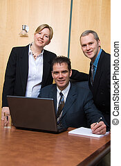 3 stong - 3 business people around a laptop in a meeting