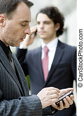 Business Communications - Two businessmen using different...