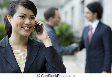 Woman On Phone - A businesswoman talking on phone with two...