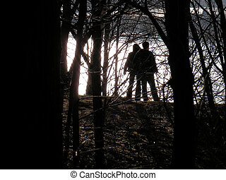 Pair in sun rays - An amorous pair stands at the forest...