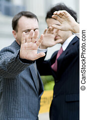 Leave Us Alone - Two businessmen avoiding the camera (focus...