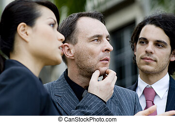 Business Thought - Three business people outside with the...