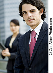 Business People Outside - A young businessman in suit...