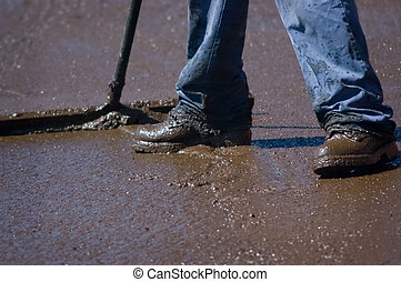 Slurry - Feet of a workman spreading slurry sealer over an...