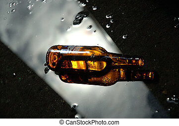 Beer bottle with reflection of clouds above in a puddle.