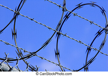 Peace and war concept - Barb wired fense with blue skies in...