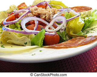 Antipasto salad in a white bowl.