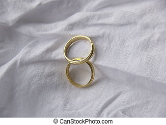 matrimony - two wedding rings on a white cloth background