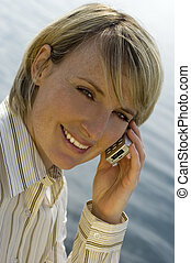 phone - young woman calling by mobile phone by sea side