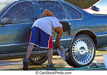 Car wash - Young man washing his car, large chrome wheels