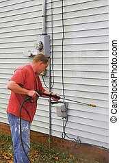 Man washing house - Contractor pressure washing house,...