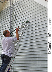 Man washing house 2 - Contractor pressure washing house,...
