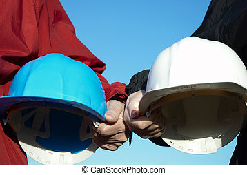 Helmets - two hard-hats blue and white color focus on hand...