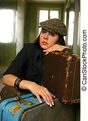 Two suitcases - The beautiful woman in a cap sits with two...