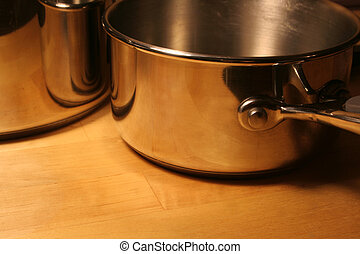 Cooking Pots - Metallic pots sitting on a wooden table.