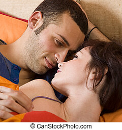 in bed - nice young couple laying on the bed