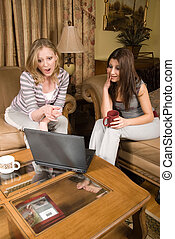 Shopping from home - Two attractive women sitting on beige...