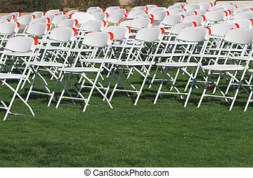Folding Chairs set up on a green lawn for an event.