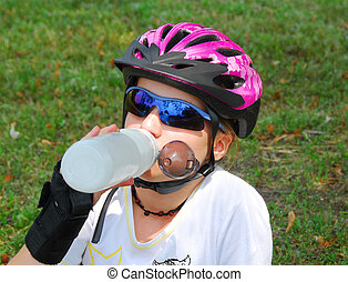 Girl drinking water - Young girl taking a break from...